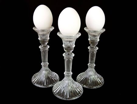 Three eggs on pedestals, full length shot, on a black background