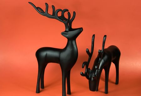 Two reindeer figurines on a red background Stock Photo