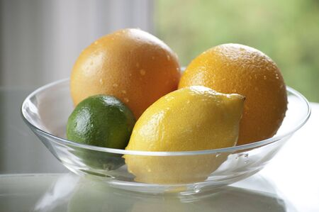 Grapefruit, orange, lemon and lime in a clear bowl Stock Photo