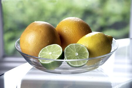A bowl of citrus fruit, with lime halves Stock Photo