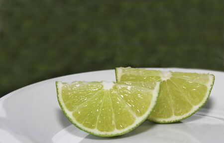 Two wedges of lime on a white plate, green background