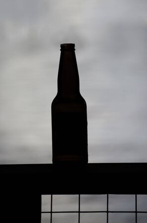 An empty beer bottle silhouetted on a lake Stock Photo