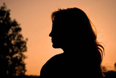 A young woman silhouettes the evening sun Stock Photo
