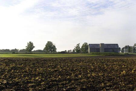 A farmers field and a barn on a light blue sky Stock Photo