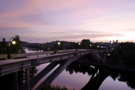 Bridge over a calm river at in a hazy dawn light