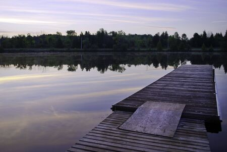 A dock on a calm river at dawn