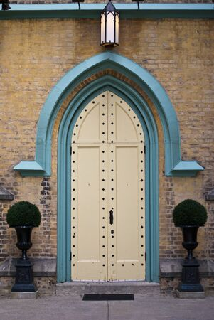 A double door church doorway, flanked by potted plants Stock Photo