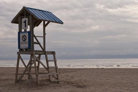 An empty lifeguard tower overlooks an empty beach and a stormy skyline