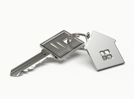 buy house: Mortgage concept. Silver key with house figure isolated on white background