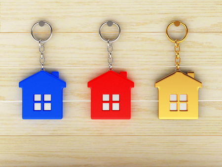 keychains: Set of colorful keychains in the form of the houses is hanging on the wooden wall Stock Photo