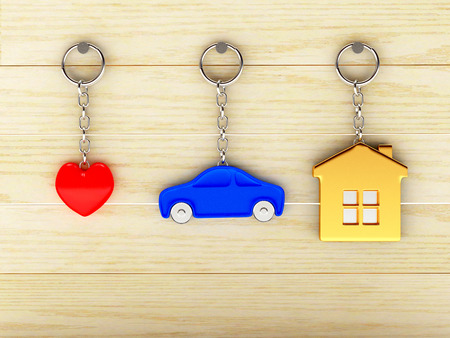 Set of colorful keychains in the form of the house, car and heart is hanging on the wooden wall