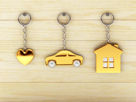 keychains: Set of golden keychains in the form of the house, car and heart is hanging on the wooden wall