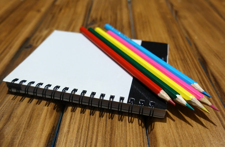 yellow notepad: Blank page notepad and colored pencils on a wooden background