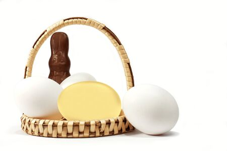 Wicker basket with chocolate Easter bunny, white and golden eggs isolated on white background. 3D illustration Stock Photo