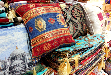 Traditional Turkish crafts. Colorful pillows with oriental ornament on the market. Stock Photo