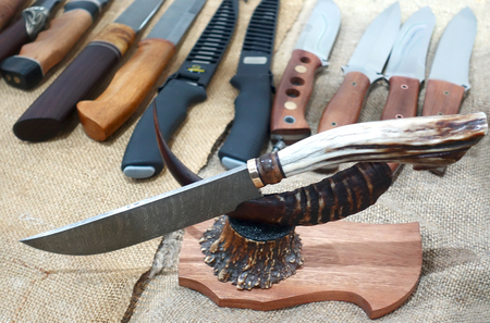 A hunting knife with a beautiful handle on a stand in the shop window