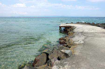 Landscape of the old breakwater and turquoise sea water. Banco de Imagens