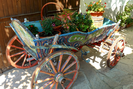 Decorative antique wooden cart filled with flowers in pots. Banco de Imagens