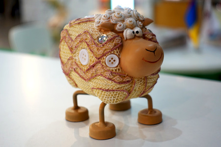 Funny decorative figure of a sheep stands on the table. 스톡 콘텐츠
