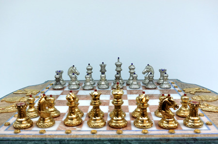 Gold and silver chess pieces on a chessboard.