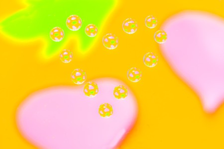 Water drops in the form of heart on a multi-coloured celebratory background Stock Photo