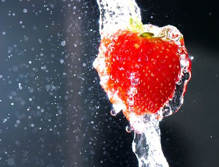 strawberry under the stream of water on a dark background photo