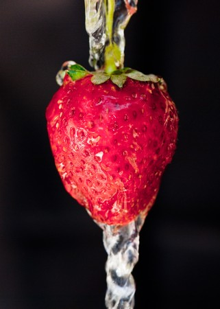 strawberry under the stream of water on a dark background