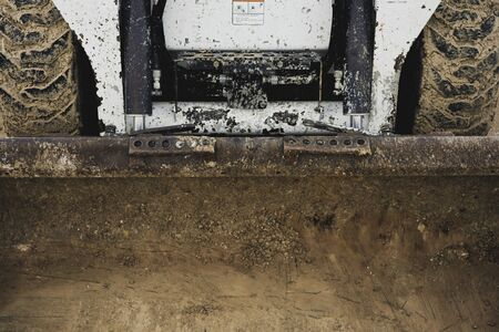 Dirty front shovel of a muddy Bobcat skid steer loader.