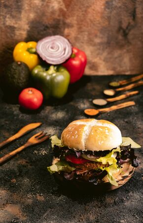 Seitan vegan burger on wooden background with vegetables. Healthy Vegan food