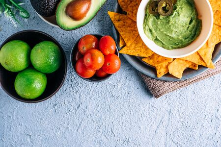 Bowl with Mexican guacamole on vintage wooden table, surrounded by tomatoes, jalapeños peppers, limes and avocados. Copyspace Stock Photo