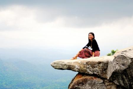 dívka posezení na kameni u útesu Reklamní fotografie