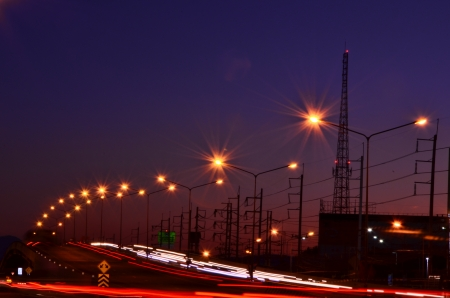 High speed traffic and blurred light trails under the overpass at night scene photo