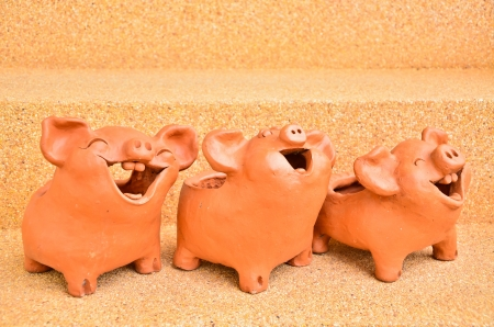 Three Pig statues laugh facing the same way. photo