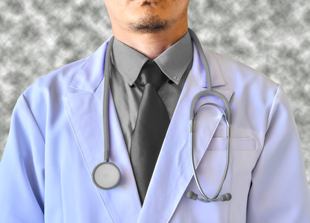 Doctor with a stethoscope close up on gray background photo