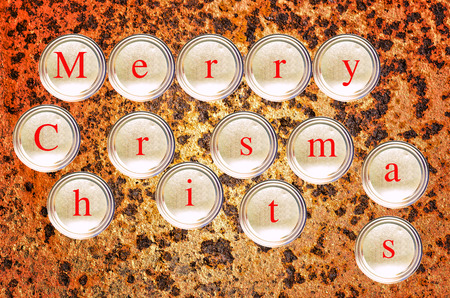 Stacked cans write merry christmas on rusty background photo