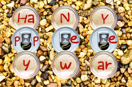 Stacked Bottom and tin cans write  happy new year on pebble background photo