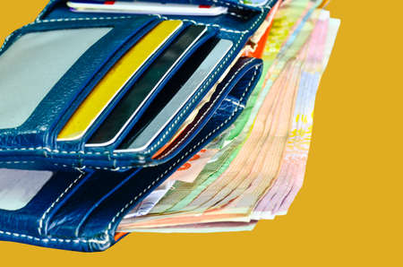 Wallet with money on yellow background photo