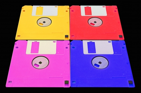 obsolete colored floppy disks on a black background photo