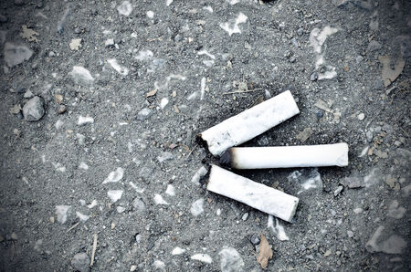 Smoked cigarette on a ground photo