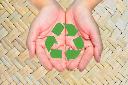 environmentalist tag: hand and recycle sign on nature background for green world concept