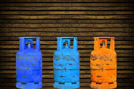cilindro de gas: Muchos cilindro de gas en la pared de madera vieja