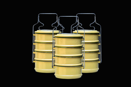 tiffin: Yellow tiffin carrier on black background