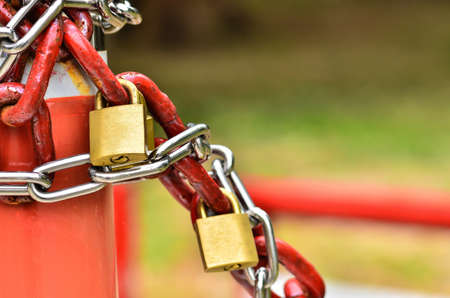 metal fastener: closed padlock with key and many chains Stock Photo
