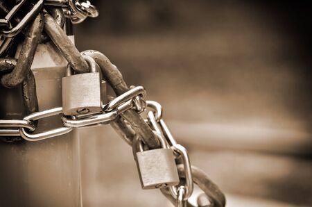 metal fastener: closed padlock with key in sepia light