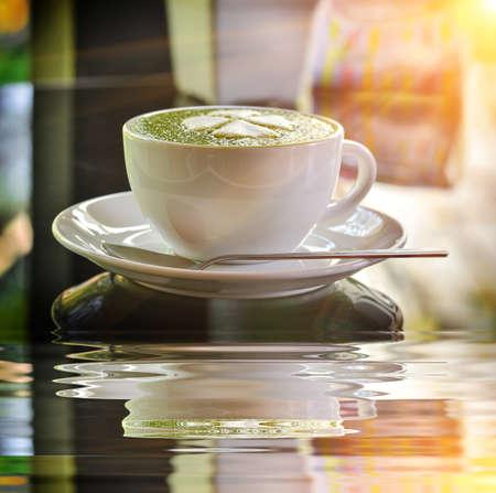 Hot green tea latte with matcha powder in morning light