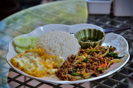 Cooked rice with spicy minced meat salad and fried egg