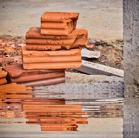 construction brick wall with reflect in water Stock Photo