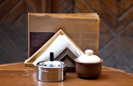 Sugar-bowl, napkin, newspaper and ash tray on the wooden table photo