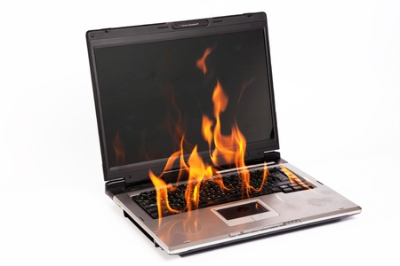 Laptop burning with fire on white background photo