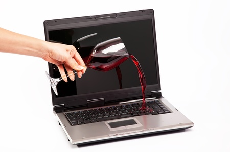 Red wine spilled on laptop keyboard on white background Stock Photo